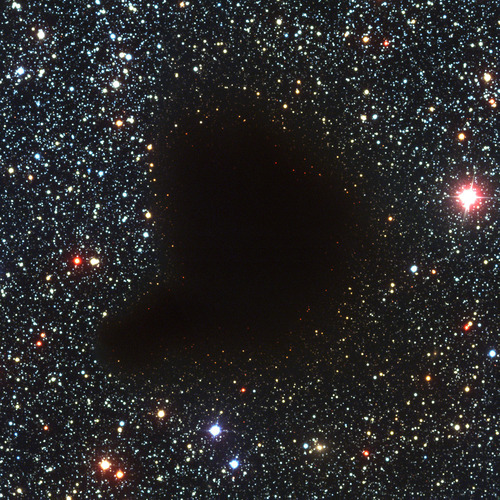 "This photograph shows an unusual sky field in the Milky Way band. It is centred on one of the classical, dark globules, known as Barnard 68 (B68) after the American astronomer, Edward E. Barnard (1857 - 1923), who included it in a list of such objects, published in 1919. It appears as a compact, opaque and rather sharply defined object against a rich, background star field. Even on this image that registers many faint stars in the area, not a single foreground star is observed. This is a clear sign that this globule must be relatively nearby. Interstellar clouds consist of gas and dust, including many molecules, some of which contain carbon atoms (i.e. organic). For a long time considered to be ""holes in the sky"", molecular clouds are now known to be among the coolest objects in the Universe (the temperature is approx. 10 K, or -263 °C). Moreover, and most importantly, they are nurseries of stars and planets. It still remains a mystery how a dark cloud like Barnard 68 at some moment begins to contract and subsequently transforms itself into hydrogen-burning stars. However, deep images of these clouds, such as this one obtained by FORS1 on VLT ANTU, may provide important clues. This small cloud seems to be in its very earliest phase of collapse. It has a diameter of only 7 light-months (approx. 0.2 pc) and it is located at a distance of about 500 light-years (160 pc) towards the southern constellation Ophiuchus (The Serpent-holder). This three-colour composite was reproduced from one blue (B), one green-yellow (V) and one near-infrared (I) exposure that were obtained with VLT ANTU and FORS1 in the early morning of March 27, 1999. The field measures 6.8x6.8 arcmin 2. The image consists of 2048x2048 pixels, each measuring 0.20 arcsec; the ""Full Resolution"" version of the photo shows all of these. North is up and East is to the left. (See also ESO Press Release eso0102.)"
